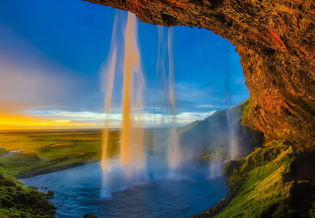 A Photograph of a waterfall in Iceland. The cream texture of the falling water is provided by using a long exposure with an ND filter. An additional Cpl filter helps to control the glare of the setting sun in the image too.