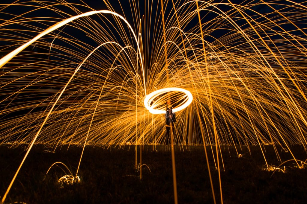 A night time photograph taken where the subject is spinning some burning steel wool for a unique effect.