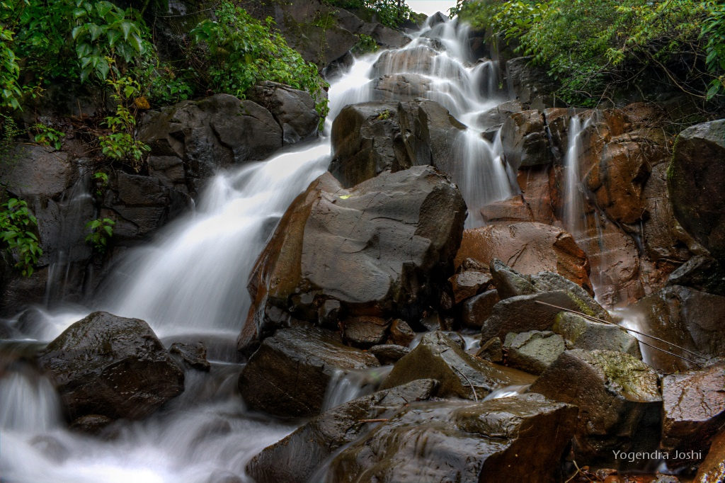 A photograph captured at the 18mm focal range with a long exposure of a waterfall along the Mulshi-Tamhini road in India.